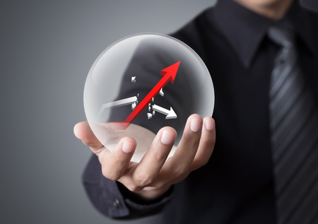 Businessman holds crystal ball with rising red graph and broken white graph Standard-Bild