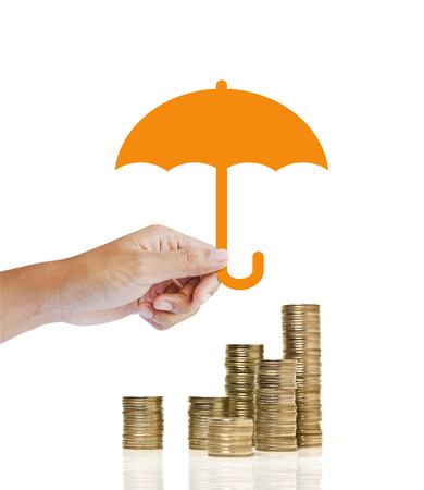 savings risk: Stacks of golden coins covered by paper umbrella. insurance concept