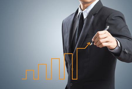 negócio: Homem de negócio que desenha a carta de crescimento, conceito do sucesso