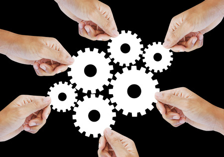 Teamwork works together to build a cog wheel gear system, Business concept. Stock Photo