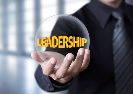 work ethic responsibilities: Leadership symbol in businessman hand, Businessman showing Leadership text in crystal ball Stock Photo