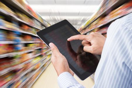 Businessman vérifier l'inventaire dans un supermarché sur tablette tactile. Motion blur Contexte Banque d'images - 57364060