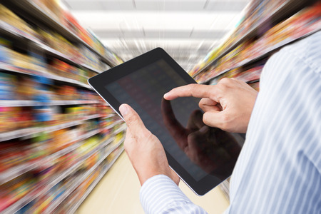 Businessman checking inventory in supermarket on touchscreen tablet. Motion blur Background Archivio Fotografico