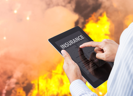 fire damage: Man pointing at insurance wording on tablet with fire background Stock Photo