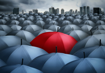red umbrella outstanding from the others. Stock Photo