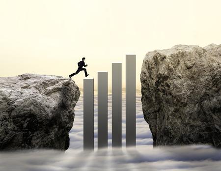 obstacle: hombre de negocios salta al otro lado de desafío con el aumento de gráfico Foto de archivo