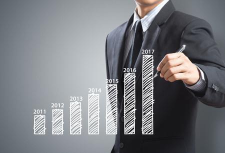 yoy: Businessman writing growing graph, year 2017 Stock Photo
