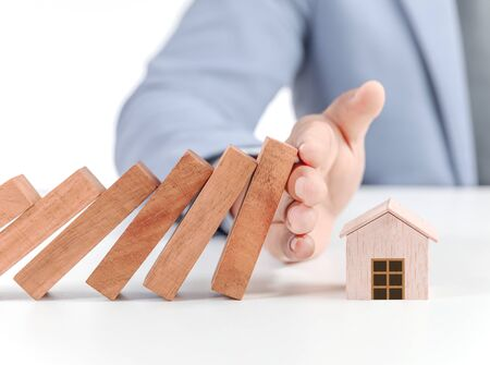 businessman covering home with hands, insurance concept