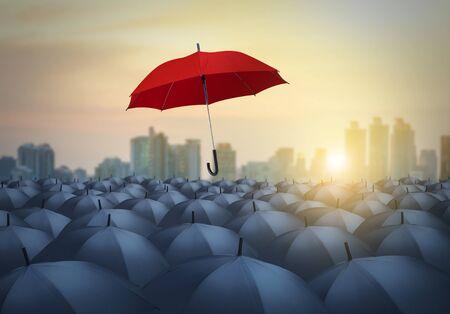 unique red umbrella among black umbrellas with city   background