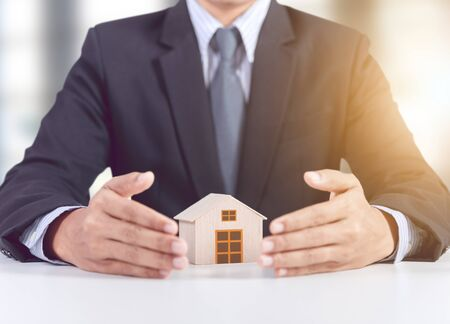 businessman hand cover wooden home model, insurance concept