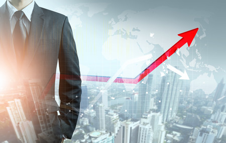 Businessman point at increasing graph and decreasing broken graph   with city background