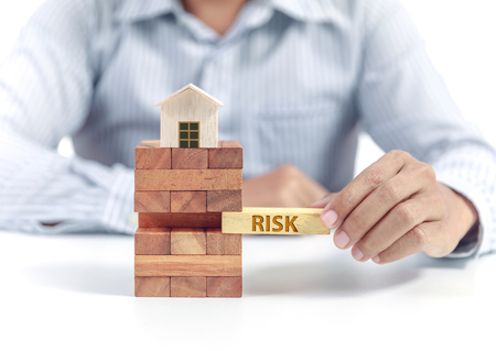Businessman hold wooden bloc with wording risk, insurance concept