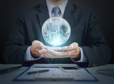 businessman hand hold crystal ball with building inside Imagens