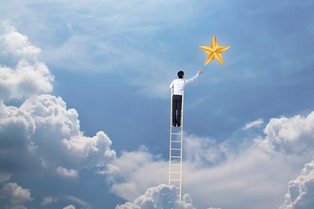 homme d & # 39; affaires grimper sur l & # 39; échelle pour atteindre le concept étoile, succès et gagner
