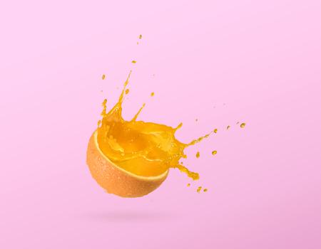 Slice of orange, orange juice splash isolated on plain