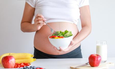 Pregnant woman eat vegetable salad, fruit, juice, milk, healthy food