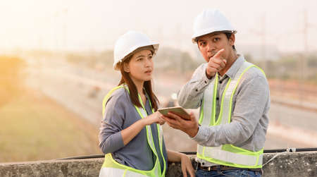 Male and female engineer discuss and use digital tablet with motorway background
