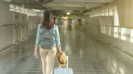 Asian woman walk with luggage and backpack at the airport terminal walkway