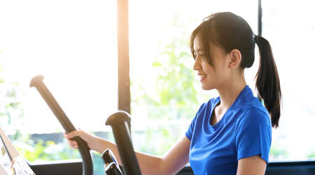 Asian woman exercise on elliptical machine in a gym 免版税图像
