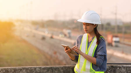 female engineer discuss and use digital tablet with motorway background 免版税图像