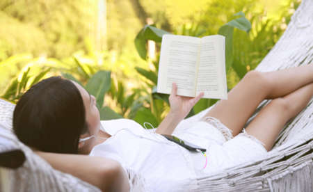 Asian woman relax and read a book in hammock