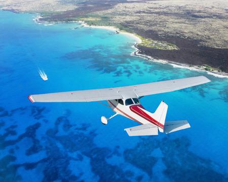 青い海の上を飛んでいる飛行機 写真素材