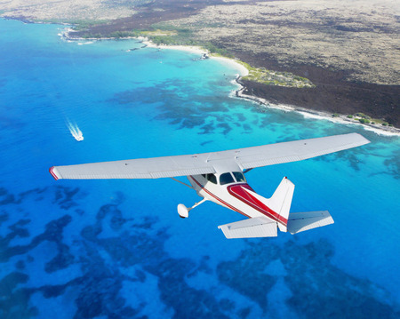 plane flying above blue ocean
