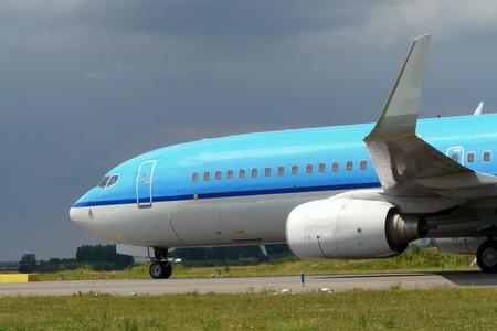 blue plane taxiing towards runway