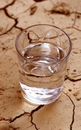 ahorrar agua: medio vaso de agua sobre la tierra agrietada