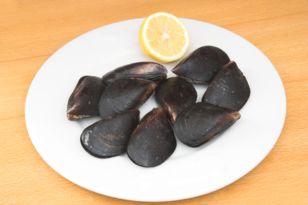appetiser: mussels and lemon placed on wooden table