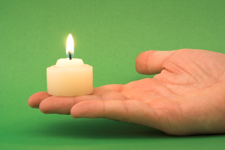 closeups: hand holding a candle (green background)