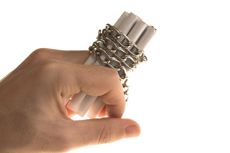 image of a hand holding loads of cigarettes that were tied with chain photo