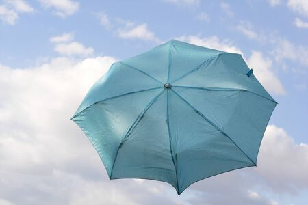 blown away: blue umbrella floating in the sky
