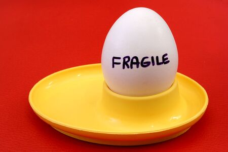 eggcup: egg on yellow eggcup the word fragile written on it Stock Photo