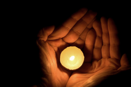 tealight: image of hand holding a tealight candle in hand