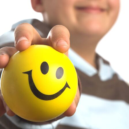 boy holding a toy  ball  with a smiley face on it