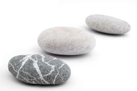 three pebbles placed on white background  shallow  depth of field
