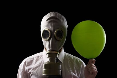fetish wear: businessman wearing  gas mask and  holing a green  baloon