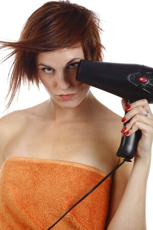 young attractive woman drying her hair with a hair dryer photo