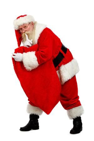 father christmas carrying his sack as he tip toes Stock Photo