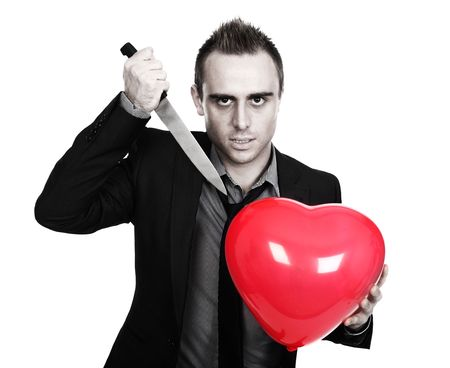 heartbreaker: young man holding a heart shaped balloon and a knife