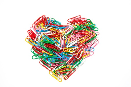 Multi color paper clips arranged in heart shape on isolated white background  photo
