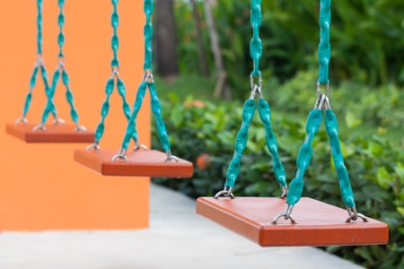 Closeup of swings in a children play area at park  photo