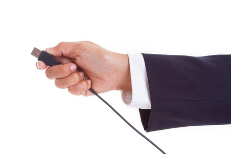 unplug: Businessman hand holding USB cable