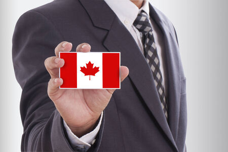 Businessman in suit holding a business card with a Canada Flag photo