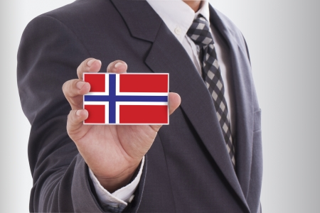 Businessman in suit holding a business card with a Norway Flag photo