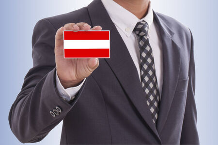 Businessman in suit hand holding a business card with Austria Flag  photo