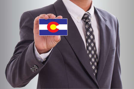 Businessman in suit holding a business card with Colorado Flag