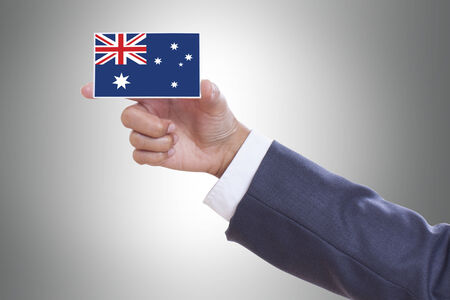 Businessman hand holding a business card with Australia flag photo
