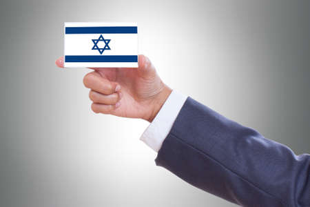 Businessman hand holding a business card with a Israel flag photo